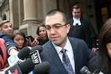 Faruk Orman, wearing glasses and a suit, walks out of court as he is filmed and photographed by media.