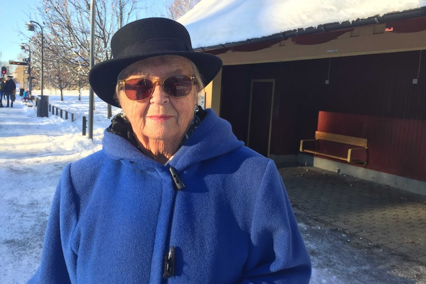 Johan's mother Gunilla stands on a snow-covered street wearing a blue coat and a black hat.