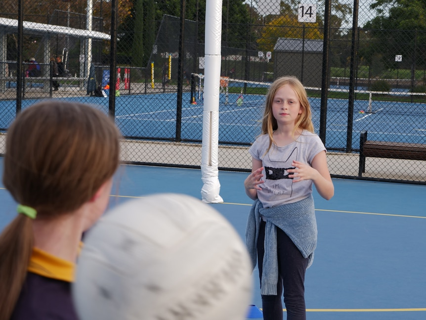 A girl with brown hair throws a netball to a young girl with strawberry blonde hair and a grey shirt