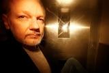 A photo of Julian Assange taken through the window of a police van