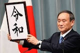 """Japan's Chief Cabinet Secretary Yoshihide Suga holds a sign to unveil the name of new era """"Reiwa""""."""
