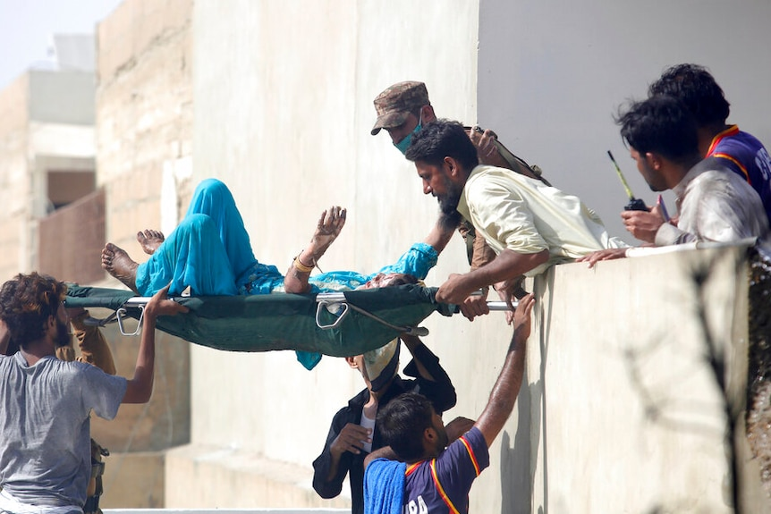 Volunteers carry an injured person at the site of a plane crash in Karachi, Pakistan.