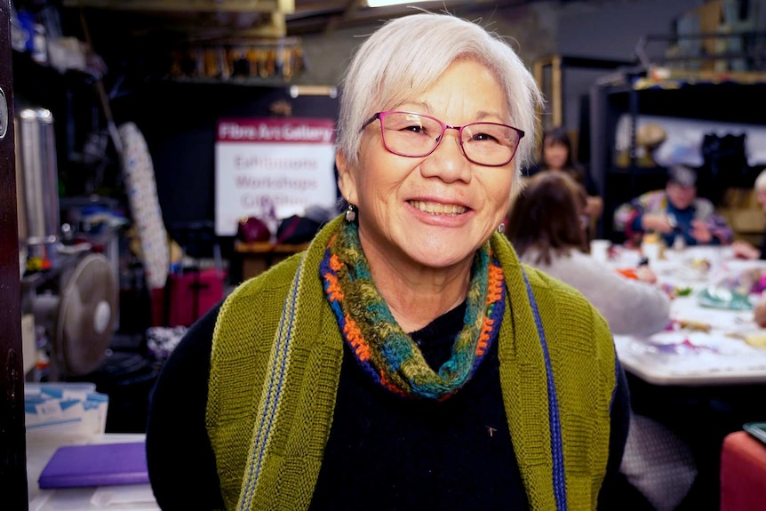 A lady with silver hair and a green cardigan with a group of textile artists in the background