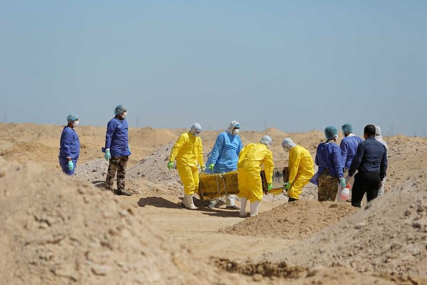 People in full hazmat gear carry a coffin through the desert