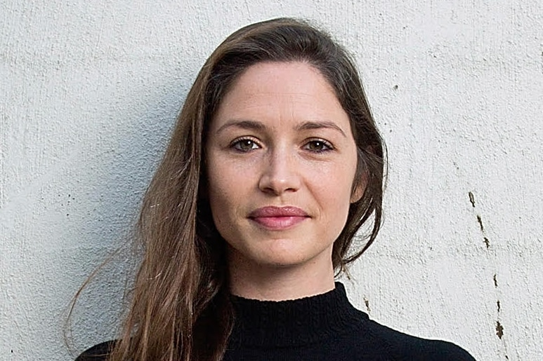 A woman in a black jumper with long brown hair.
