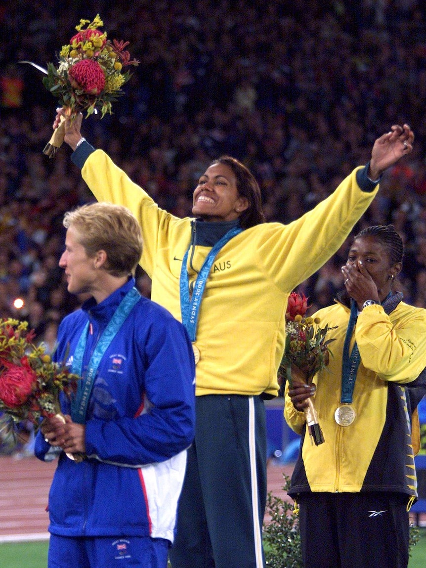 Australia's Cathy Freeman (C) waves to the crowd from the medal winners podium at the Sydney Olympic Games, September 25, 2000.