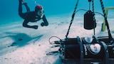A diver looks at some very large black equipment underwater.