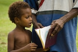 A child in Madang province reads the Bible with his father