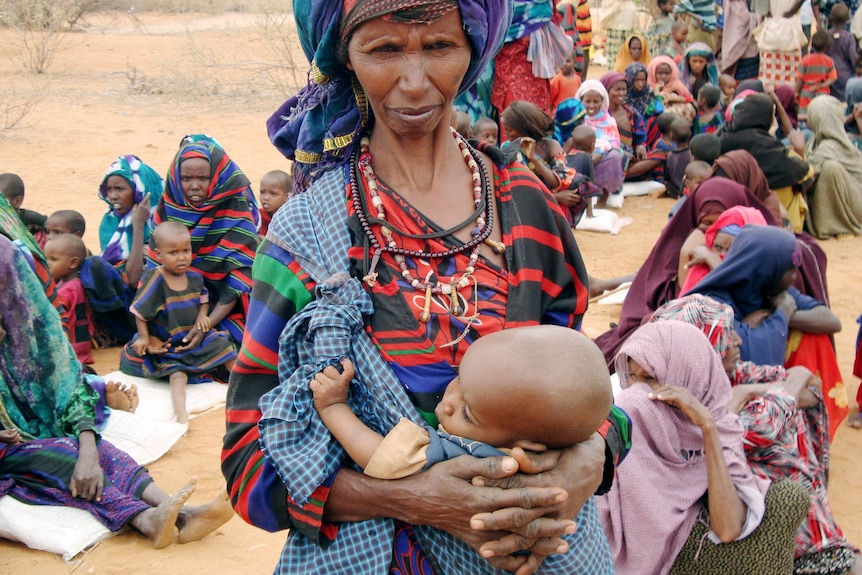 Starving and desperate: refugees and children wait to go to a refugee camp in Ethiopia