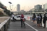 Police and security guards attempt to remove a car from a boardwalk along the Brisbane River.