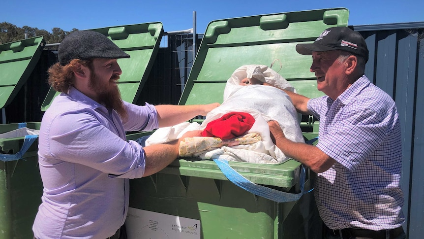 Two men standing sideways in front of a waist-high green bin full of clothes.