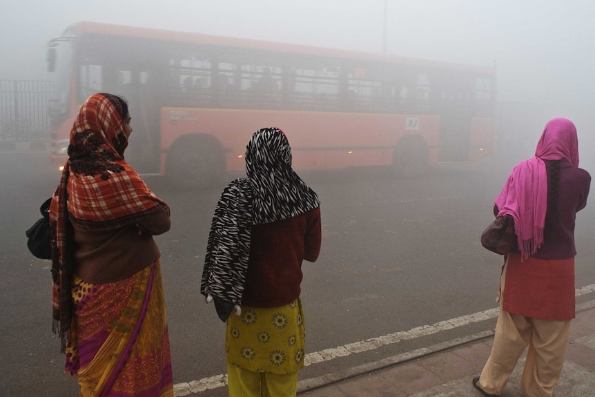 Indian commuters wait for a bus early on a polluted morning in New Delhi on January 31, 2013.