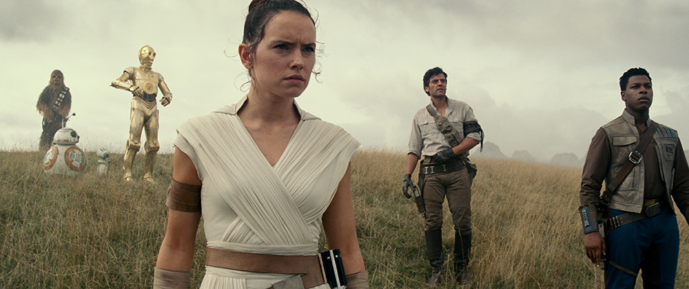 Chewbacca, two small droids, C-3PO, Daisy Ridley, Oscar Isaac and John Boyega stand in dry grassland with serious expressions.
