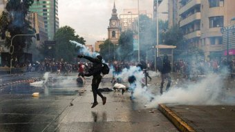 Protester throwing object in the middle of a street with protesters and tear gas in the background.