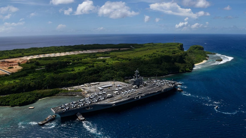 The aircraft carrier USS Theodore Roosevelt departs Naval Base Guam.