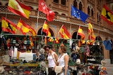 Two women walk past a stall in Madrid selling Spanish flags.