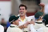 Pat Cummins celebrates as teammates rush to him after taking a wicket