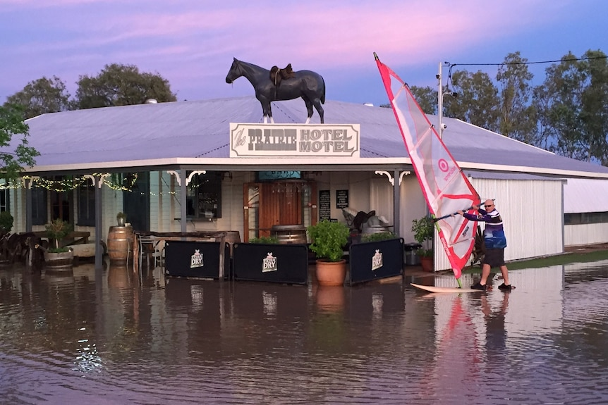a man stands on a wind surfer outside a hotel where flood water has risen to the front of