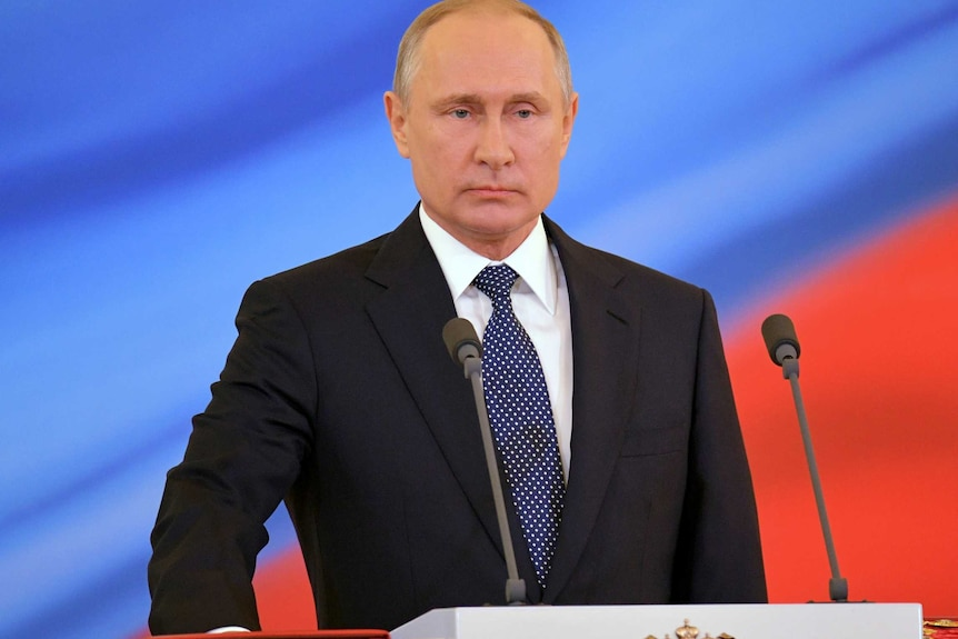 Putin is seen standing on a podium, his hand on the constitution.