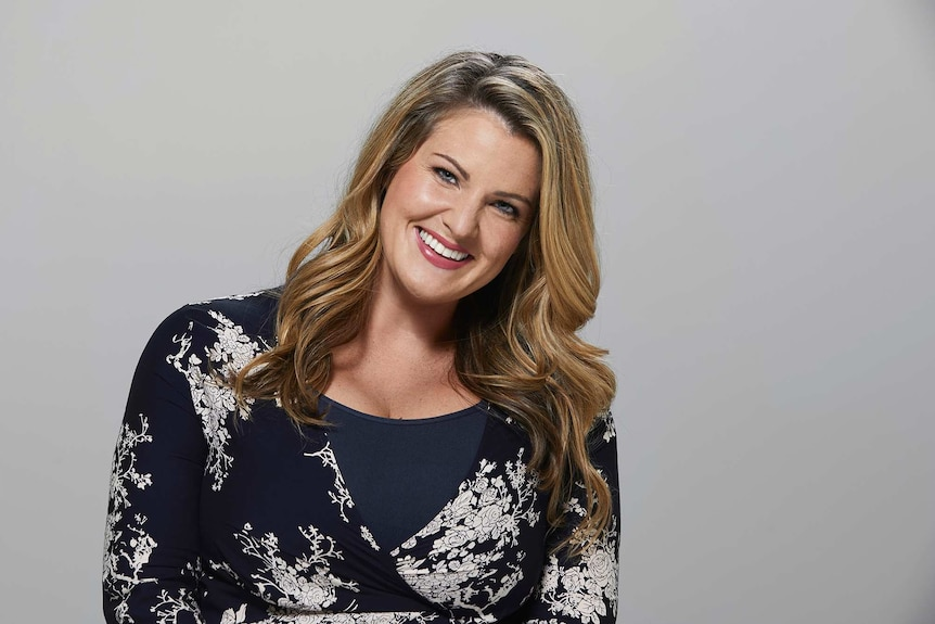 Comedian Nikki Britton photographed in a studio, smiling at the camera and wearing a floral wrap dress. She goes on dates alone.