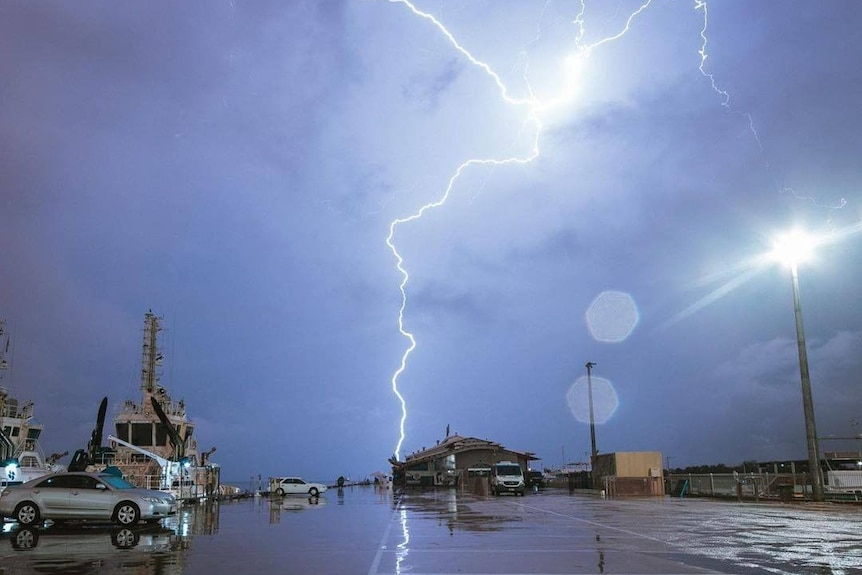 A storm can be seen cracking over a wharf.