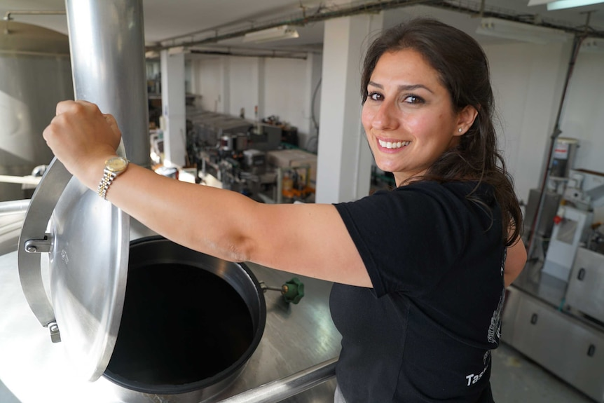 A smiling woman lifts the lid on a steel vat