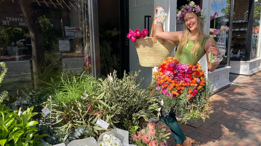 A smiling woman wearing a brightly coloured skirt made of flowers and a flower crown holds a basket of flowers