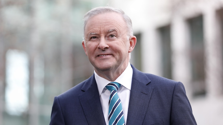Albanese is outdoors, wearing a blue suit with blue and black tie, and smiling.