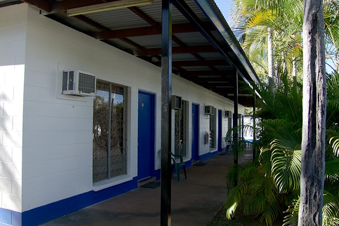 A walkway with palm fronds outside two budget hotel rooms with blue doors.