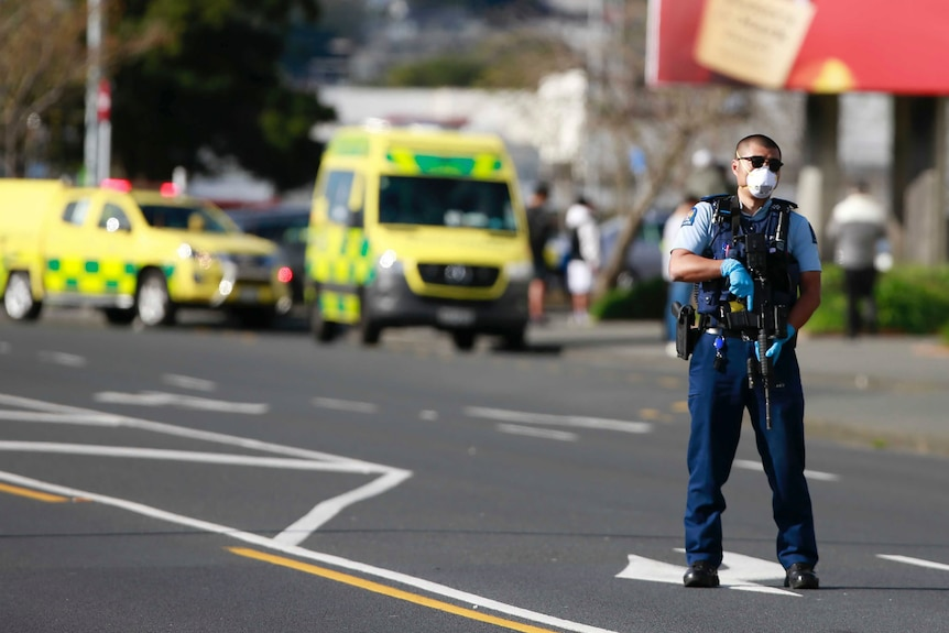 A police officer holding a machine gun stands on a road with ambulances behind him