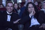 Two men sitting in a dark cinema.
