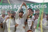 Australia captain Tim Paine lifts the Ashes Urn as his Australian teammates smile, laugh and spray champagne. Streamers fly.