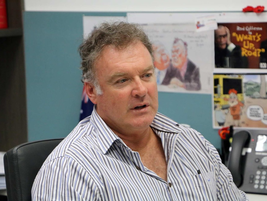 Senator Rodney Culleton at his West Perth Office, with Australian flag behind him.
