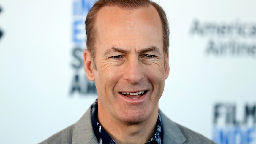 Bob Odenkirk smiles while wearing a light grey suit.