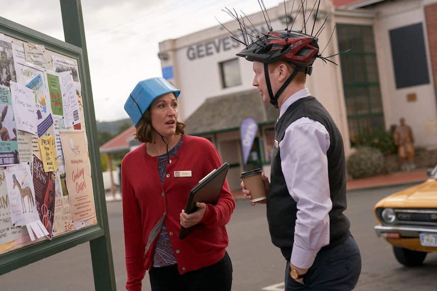 A woman and a man look at each other while wearing an ice cream tub and a spiky bicycle helmet on their heads.