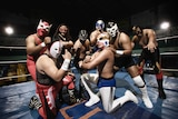 Wrestlers wearing masks stand fiercely in the ring.