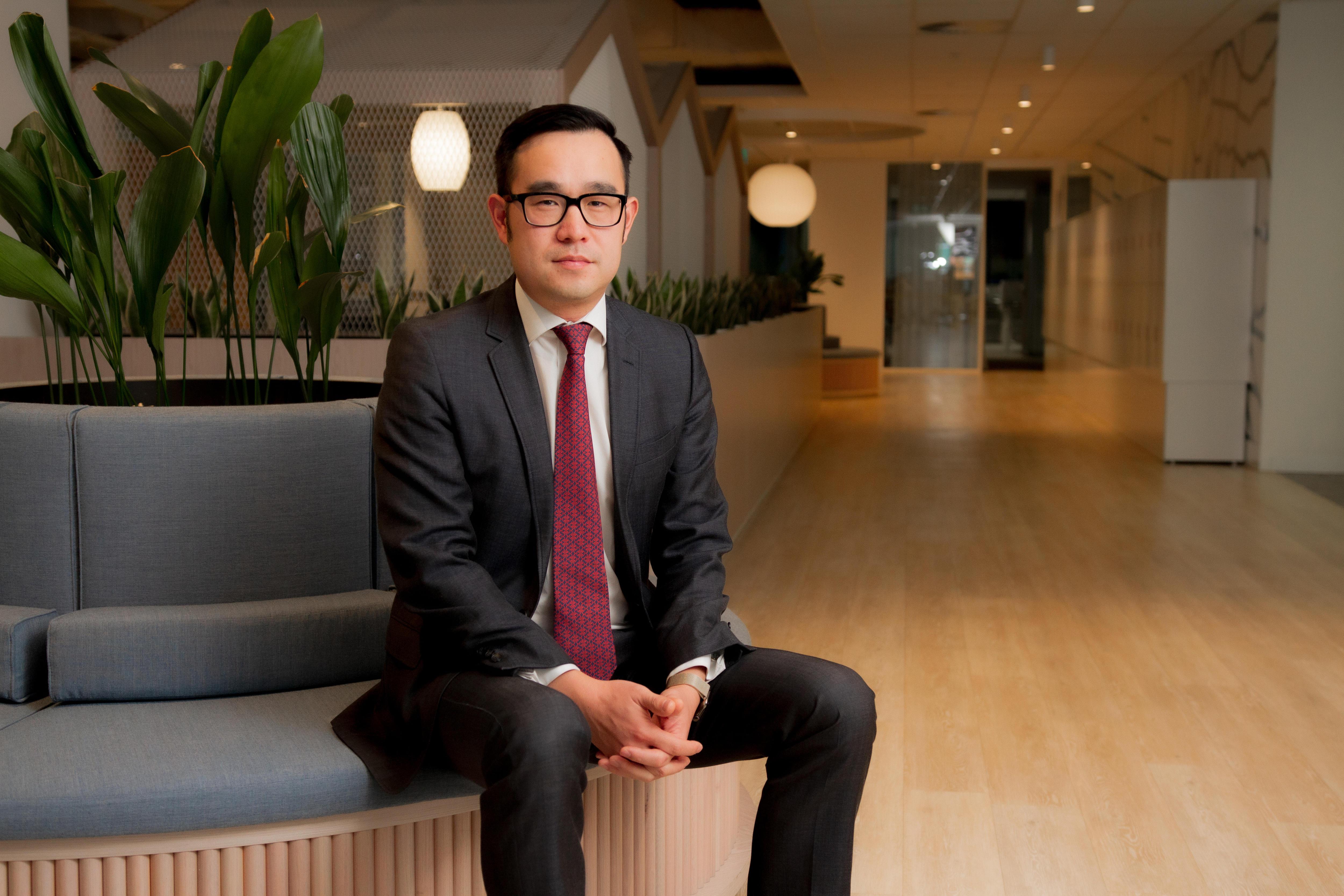 Tim Loh sitting in a foyer in deak grey suit