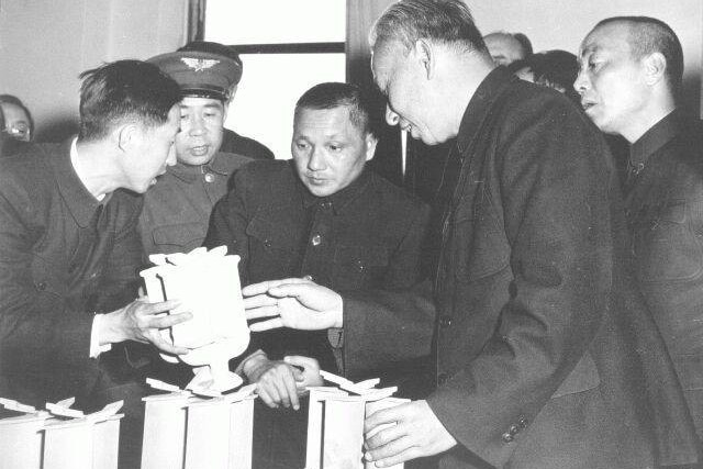 A black and white photo of Deng Xiaoping at a factory