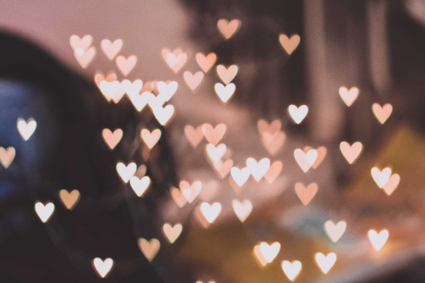 Luminescent hearts both in and out of focus against a darker backdrop.