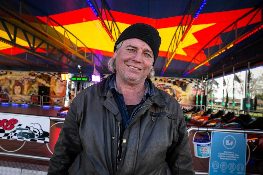 Elwin Bell sits in front of a dodgem car ride.