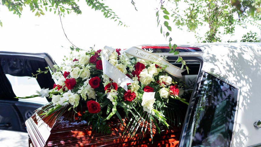 A casket with red roses on top in the back of a hearse.