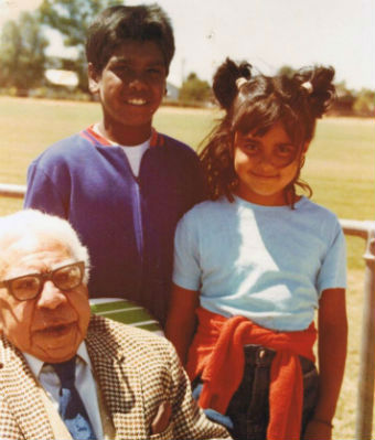 Two children pose with their grandfather