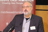 A bearded man with grey hair and a beard dressed in a shirt and suit jacket speaks from a podium