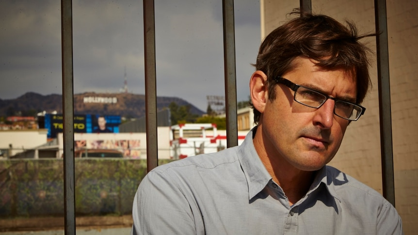 Louis Theroux standing in front of a fence