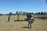 Two forensic police officers examine a grassy paddock in Armidale with an excavator used to dig the ground.