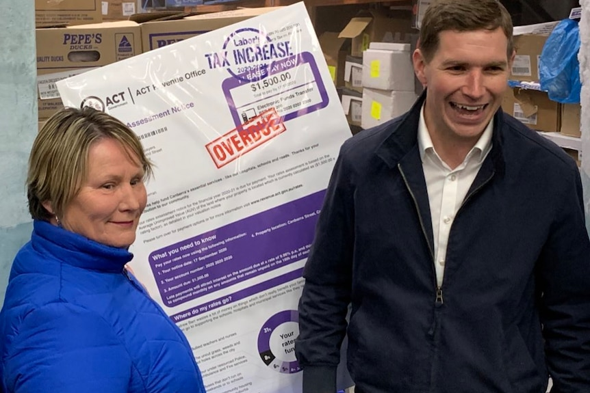 Alistair Coe and Nicole Lawder stand in a commercial freezer with a print out of a giant rates bill.