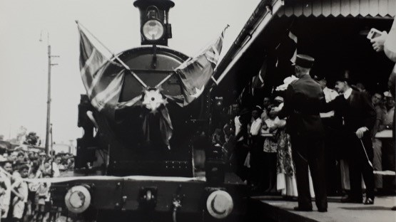 A black and white image of a train arriving at a station in 1913, with people standing on the platform