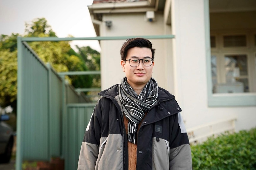 David Le stands with glasses and a scarf outside a house.