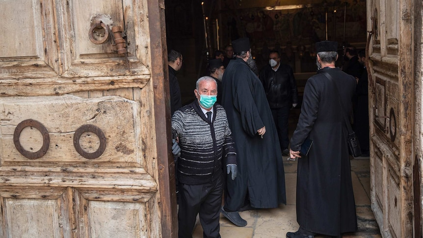 Wajeeh Nuseibeh wearing face mask closing doors to the Holy Sepulchre, with religious leaders dressed in black inside.