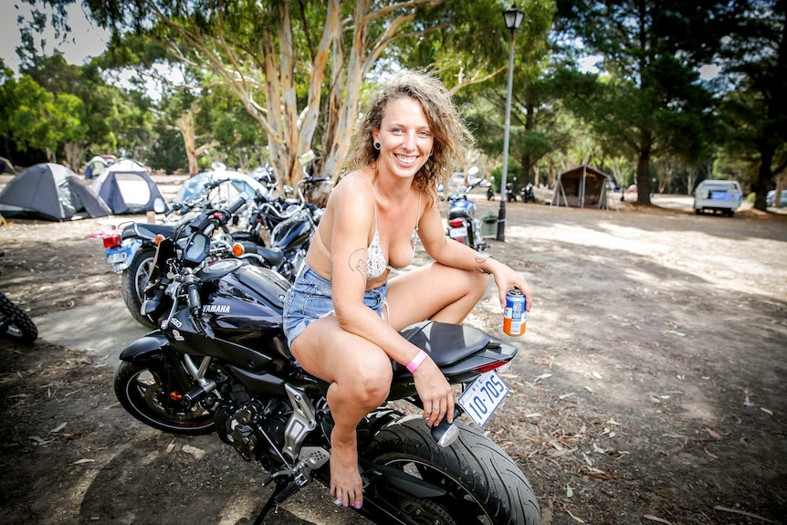 A woman smiles while squatting on a motorbike with a beer in hand